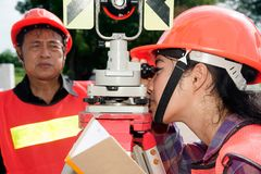 Surveyor or Engineer setting prism reflector with partner on the field. Surveyor or Engineer setting measure by prism reflector with partner on the field stock photo