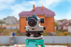 Surveyor equipment optical level or theodolite outdoors at construction site directed on building. Surveyor equipment optical level or theodolite outdoors at Royalty Free Stock Photos
