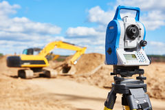 Surveyor equipment theodolie at construction site with excavator Stock Photography