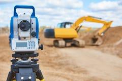 Surveyor equipment theodolie at construction site with excavator. Surveyor equipment tacheometer or theodolite outdoors at construction site in front of loader Stock Photo