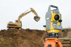 Surveyor equipment theodolite. On tripod at building area in front of working construction machinery loader Stock Images