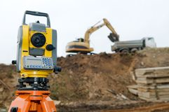 Surveyor equipment theodolite. On tripod at building area in front of working construction machinery loader Royalty Free Stock Images