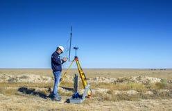 Surveyor. Geodetic surveyor installs the GPS equipment in the desert Betpakdala royalty free stock photo