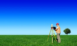 Surveyor on green field. Blue sky in background. Surveyor on green field, blue sky and tree in background royalty free stock images