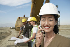 Surveyor in Hardhat In Front Of Heavy Machinery Using Cellphone On Site Stock Image