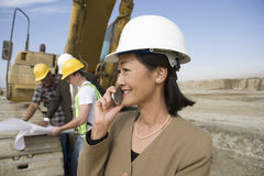 Surveyor in Hardhat In Front Of Workers Using Cellphone On Site Royalty Free Stock Photo