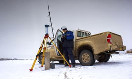 Surveyor. Surveyor installs equipment GPS in the winter in the steppes of southern Kazakhstan stock images