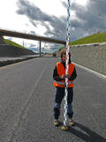 Surveyor with levelling staff. Young curly surveyor levelling on highway royalty free stock photo