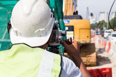 Surveyor operating the dumpy automatic level instrument at const Stock Image