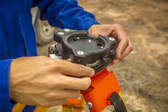 Surveyor. Sets levels to the tripod for surveying instruments. June 2015 royalty free stock image