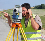 Surveyor with theodolite. Showing a direction Royalty Free Stock Photos