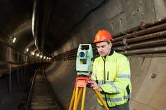 Surveyor with theodolite level at underground railway tunnel construction work Stock Photos
