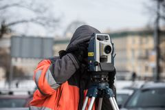 The surveyor with the theodolite makes measurements in the cente. St. Petersburg, Russia - March 28, 2018: A young male surveyor makes the necessary measurements Royalty Free Stock Photos