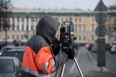 The surveyor with the theodolite makes measurements in the cente. St. Petersburg, Russia - March 28, 2018: A young male surveyor makes the necessary measurements Royalty Free Stock Images