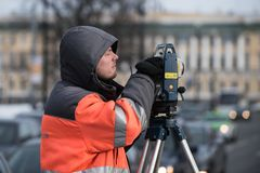 The surveyor with the theodolite makes measurements in the cente. St. Petersburg, Russia - March 28, 2018: A young male surveyor makes the necessary measurements Stock Photos