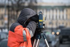 The surveyor with the theodolite makes measurements in the cente. St. Petersburg, Russia - March 28, 2018: A young male surveyor makes the necessary measurements Stock Photography