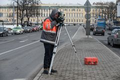 The surveyor with the theodolite makes measurements in the cente. St. Petersburg, Russia - March 28, 2018: A young male surveyor makes the necessary measurements Stock Image