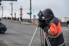 The surveyor with the theodolite makes measurements in the cente. St. Petersburg, Russia - March 28, 2018: A young male surveyor makes the necessary measurements Stock Photo