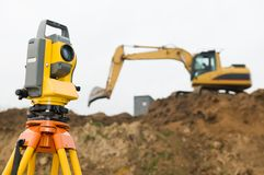 Surveyor theodolite on tripod. Surveyor equipment theodolite on tripod at building area in front of working construction machinery loader Stock Photo