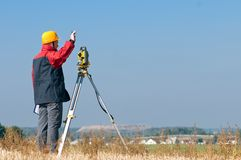 Surveyor theodolite worker. Surveyor worker making measurement in a field with theodolite total station equipment Stock Image