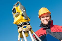 Surveyor theodolite worker. Smiley Surveyor worker making measurement in a field with theodolite total station equipment Royalty Free Stock Photography
