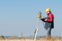 Surveyor theodolite worker. Surveyor worker making measurement in a field with theodolite total station equipment Stock Photo