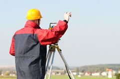 Surveyor theodolite works. Surveyor worker making measurement in a field with theodolite total station equipment Royalty Free Stock Photography