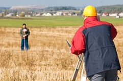 Surveyor theodolite works. Two surveyor workers with theodolite total station equipment outdoors Royalty Free Stock Photo