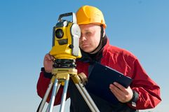 Surveyor theodolite works. Surveyor worker making measurement in a field with theodolite total station equipment Stock Photos