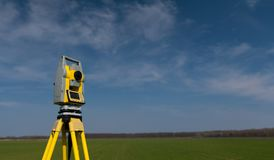 Surveyor equipment on a tripod in the field. Surveyor tools for measuring forest and land. Yellow theodolite on a tripod with green and blue background. Geodesy royalty free stock image