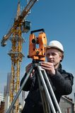 Surveyor with transit level. Worker surveyor measuring distances, elevations and directions on construction site by theodolite level transit equipment Stock Image
