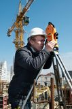 Surveyor with transit level. Worker surveyor measuring distances, elevations and directions on construction site by theodolite level transit equipment Royalty Free Stock Image