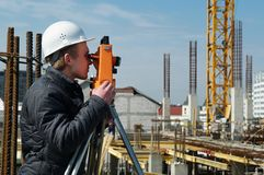 Surveyor with transit level. Worker surveyor measuring distances, elevations and directions on construction site by theodolite level transit equipment Stock Images