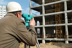 Surveyor with transit level. Worker surveyor measuring distances, elevations and directions on construction site by theodolite level transit equipment Royalty Free Stock Photography