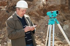 Surveyor with transit level. Worker surveyor measuring distances, elevations and directions on construction site by theodolite level transit equipment Royalty Free Stock Photo