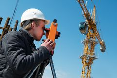 Surveyor with transit level. Worker surveyor measuring distances, elevations and directions on construction site by theodolite level transit equipment Royalty Free Stock Images