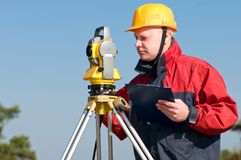 Surveyor at work. Surveyor worker making measurement in a field with theodolite total station equipment stock image