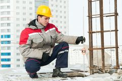 Surveyor at work. Surveyor worker assistant working at construction site in winter with survey target stock photography