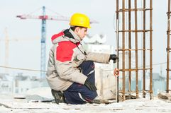 Surveyor at work. Surveyor worker assistant working at construction site in winter with survey target royalty free stock image