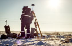 Surveyor. Surveyor work in the steppe with GPS equipment in the winter stock photo