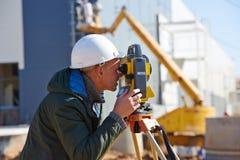 Surveyor worker with theodolite. Surveyor builder worker with theodolite transit equipment at construction site outdoors during surveying work stock photos