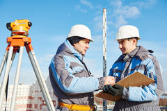 Surveyor workers with level at construction site Royalty Free Stock Image