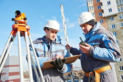 Surveyor workers with level at construction site. Two surveyor builders working with theodolite equipment at construction site stock image