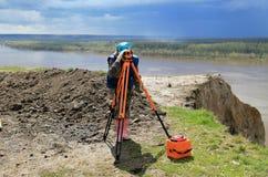 Surveyor working. Surveyor using geodetic equipment to survey a remote site royalty free stock photo