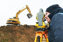 Surveyor works with theodolite. Surveyor worker make data collection with total station theodolite at construction site Royalty Free Stock Image