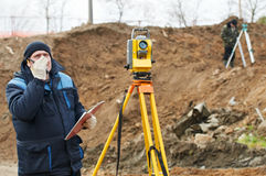 Surveyor works with theodolite. Surveyor worker make data collection with total station theodolite at construction site Stock Image