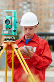 Surveyor works with theodolite. One surveyor worker with theodolite equipmant outdoors input the data Royalty Free Stock Photos