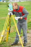 Surveyor works with theodolite. One surveyor worker working with theodolite transit equipment at spring field construction site outdoors Royalty Free Stock Images