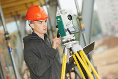 Surveyor works with theodolite. One surveyor worker working with theodolite transit equipment at road construction site outdoors Stock Photo