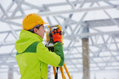Surveyor works with theodolite. Female surveyor worker working with theodolite transit equipment at building construction site outdoors stock photography